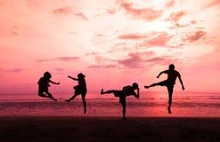 青年人在海滩跳在日落在泰国, Mae nam海滩, Bo Phut,苏梅岛 免版税库存照片