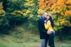 青年人在秋天公园 黄色树和叶子 愉快的年轻家庭观念 免版税库存照片