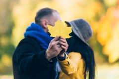 青年人在秋天公园 黄色树和叶子 愉快的年轻家庭观念 免版税图库摄影