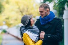 青年人在秋天公园 黄色树和叶子 愉快的年轻家庭观念 免版税库存图片