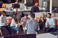 青年人小组在现代办公室有队会议和激发灵感,当工作在膝上型计算机和饮用的咖啡时 免版税库存照片