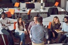 青年人小组在现代办公室有队会议和激发灵感,当工作在膝上型计算机和饮用的咖啡时 库存图片