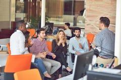 青年人小组在现代办公室有队会议和激发灵感,当工作在膝上型计算机和饮用的咖啡时 图库摄影