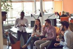 青年人小组在现代办公室有队会议和激发灵感,当工作在膝上型计算机和饮用的咖啡时 免版税图库摄影