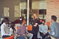 青年人小组在现代办公室有队会议和激发灵感,当工作在膝上型计算机和饮用的咖啡时 库存照片