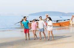 青年人小组海滩暑假,愉快的微笑的朋友走的海边 免版税库存照片