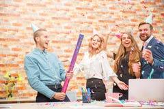 青年人庆祝某事在一个公司党在办公室 免版税库存照片