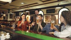 青年人庆祝某事在酒吧的啤酒 他们提出多士、叮当响的玻璃和瓶 股票录像