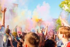 青年人获得乐趣在Holifest,投掷的五颜六色的粉末期间在天空中 免版税库存图片