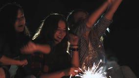 青年人野餐有篝火的在海滩在晚上 唱歌曲和弹吉他的快乐的朋友 暂挂 影视素材