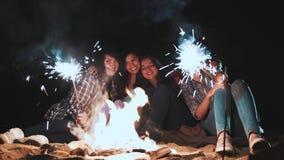 青年人野餐有篝火的在海滩在晚上 唱歌曲和弹吉他的快乐的朋友 暂挂 股票录像