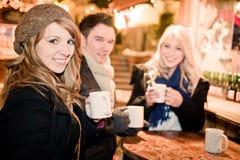 青年人饮用的打孔机在圣诞节市场上 免版税库存照片