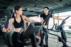 青年人-小组妇女和人-做骑自行车在健身的,健身房的行使在xt的人健身房的体育 免版税库存照片