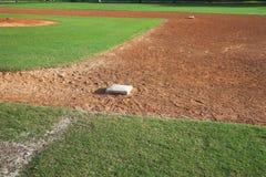 青年从一垒边的棒球耕地在好日子 库存图片