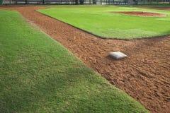 青年从一垒边的棒球耕地在早晨光 免版税库存照片