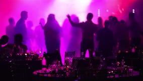 青年党在餐馆或夜总会,与酒精的以剪影为背景的宴会桌和食物 影视素材