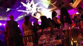 青年党在餐馆或夜总会,与酒精的以剪影为背景的宴会桌和食物 股票视频