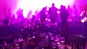 青年党在餐馆或夜总会,与酒精的以剪影为背景的宴会桌和食物 股票录像