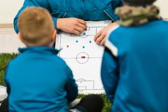青年教练孩子的足球教练 男孩足球运动员听的教练战术和诱导谈话 免版税图库摄影