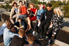 青年旅行欧洲坐屋顶唱歌享受微笑 免版税图库摄影