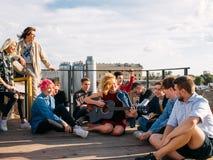 青年旅行欧洲坐屋顶唱歌享受微笑 图库摄影