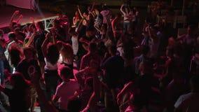 青年时期,迪斯科聚会,在明亮的照明设备的人群跳舞夜生活在慢动作,跳舞在夜总会的青年人 股票视频