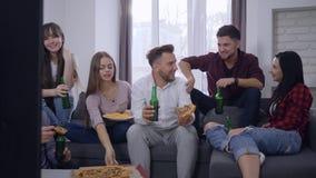 青年汇聚,有女孩乐趣的愉快的朋友人与比萨和瓶装啤酒沟通,当看电视在时 股票视频