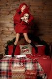 青春期前的儿童女孩在美好的旅馆客房醒和跳在她的床近装饰的圣诞树在假日 免版税图库摄影