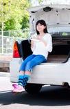青春期前的女孩坐吃午餐的后面汽车防撞器 免版税库存照片
