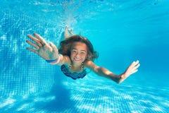 青春期前的女孩潜水画象与乐趣的在水池 库存图片