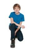 青春期前的男孩坐白色背景 免版税库存图片
