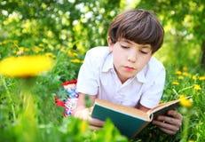 青春期前的英俊的敏锐的在夏天公园wi的男孩红色和旧书 免版税图库摄影