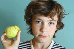 青春期前的英俊的男孩举行绿色苹果 库存照片