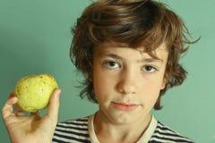 青春期前的英俊的男孩举行绿色苹果 免版税图库摄影