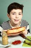 青春期前的英俊的男孩厨师他自己大热狗 库存照片