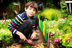 青春期前的英俊的男孩工作在开花的夏天庭院里 库存图片