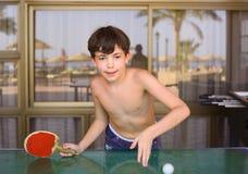 青春期前的英俊的男孩戏剧乒乓球在海滩胜地旅馆里 免版税库存照片