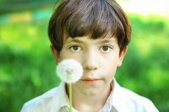 青春期前的英俊的男孩打击用蒲公英在夏天晴天 免版税图库摄影