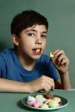 青春期前的英俊的男孩用macaron曲奇饼 免版税库存图片