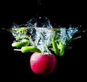 青椒和红色苹果水飞溅黑背景 免版税库存照片