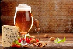 青纹干酪开胃菜和啤酒在棕色葡萄酒背景 免版税库存照片
