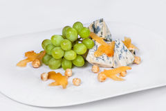 青纹干酪开胃菜用葡萄,鸡豆,杏干 在白色背景的盘 图库摄影