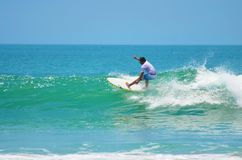青绿的冲浪者在海浪,冲浪 印度尼西亚,巴厘岛, 2011年11月10日 免版税图库摄影