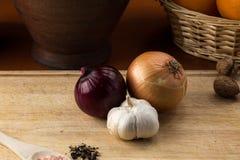 青葱、葱和大蒜在切板 免版税库存图片