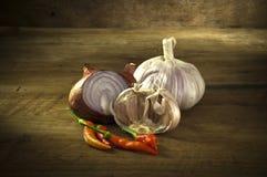 青葱,大蒜,胡椒,安置在木桌低调光 免版税库存照片