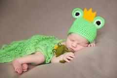 青蛙服装的逗人喜爱的新出生的婴孩 免版税库存图片