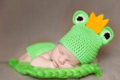 青蛙服装的逗人喜爱的新出生的婴孩 免版税库存照片