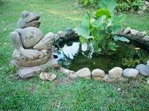 青蛙雕象在庭院里 库存照片