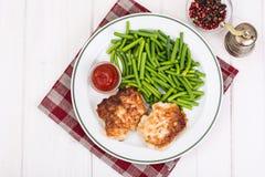 从青豆和炸肉排吃午餐在白色木桌上 免版税库存照片