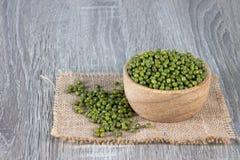 青豆溢出木碗和堆在被编织的大袋 免版税图库摄影